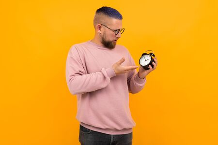 Young strong man with short black hair and glasses holds alarm clock and smiles isolated on orange background Banco de Imagens