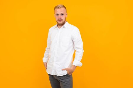 portrait of a blond young man in a white shirt on a yellow background with copy space.