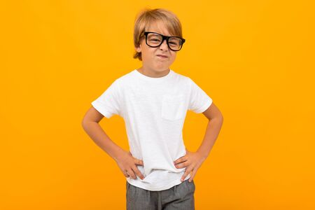 boy in a white T-shirt squinting in glasses on a yellow background with copy space. Banco de Imagens