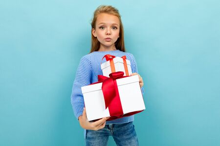 Beautiful caucasian girl holds a white boxes with gifts and has no emotions isolated on blue background