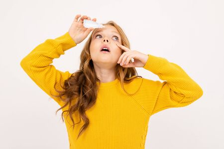 Happy teenager girl with red hair, hoody and yellow trousers holds contact lenses isolated on white background.