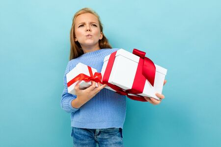 Portrait of little caucasian girl with long brow hair in blue hoody holds a white boxes with gifts isolated on blue background. Banco de Imagens