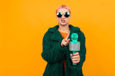 Happy caucasian woman with short pink hair in dark coat and sunglasses doesnt wants to sing into a microphone isolated on orange background Banco de Imagens