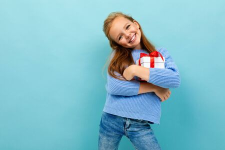 valentines day concept. little girl hugs a gift on a light blue background.