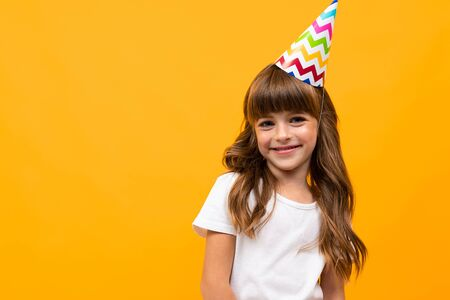 birthday girl with festive cap on a yellow background with copy space.
