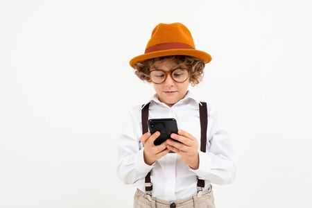 Beautiful boy with curly hair in white shirt, brown hat, glasses with black suspenders call the phone isolated on white background.