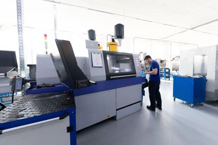 the worker in blue form looks behind work and performs tuning Banco de Imagens