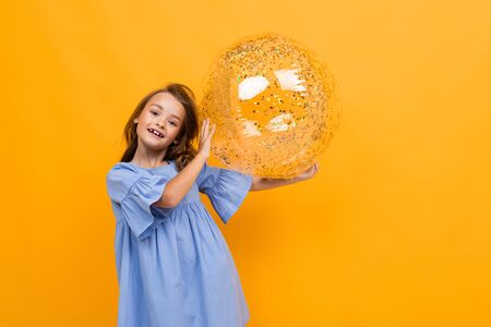 smiling attractive girl in a blue dress holds a sparkling transparent ball on a yellow background with copy space. Banco de Imagens
