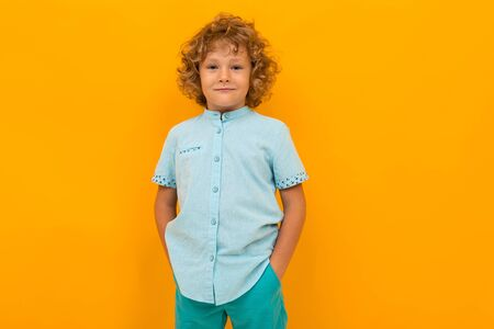 Little boy with curly hair in blue shirt and shorts isolated on yellow background Banco de Imagens