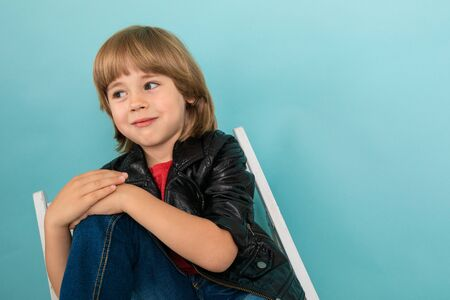 stylish male child in a leather jacket and a red T-shirt sitting on a chair on a light blue background with copy space.