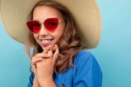Caucasian girl with wavy brown hair in blue dress, big hat, red sunglasses isolated on blue background