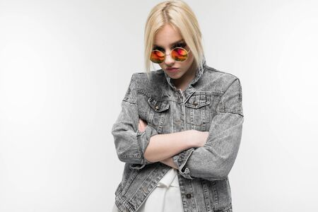 portrait of young charming joyful blonde girl in jeans jacket possing and gesticulating in round sunglasses on background