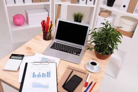 un uomo rivede i grafici e lavora con un laptop sul desktop con calcolatrice, penne, matite, carta, telefono e una pianta in ufficio.