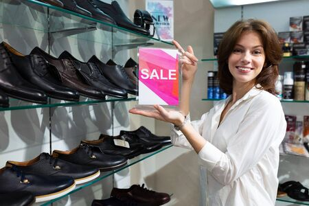 Beautiful girl chooses mans shoes in the store.