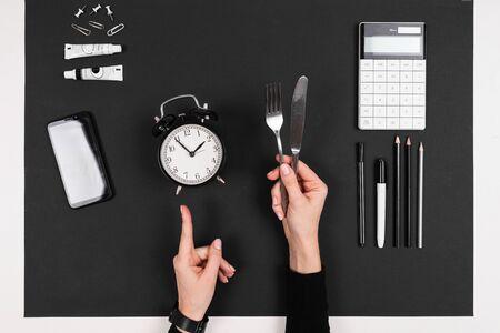 Fork, knife, laptop, calculator, pens, pencils, card, alarm clock isolated on black background