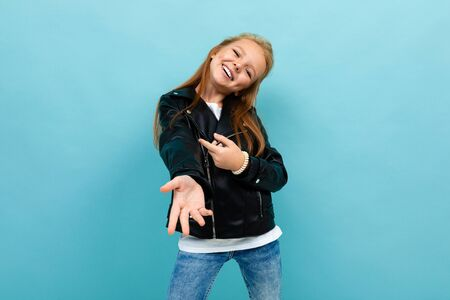 Caucasian teenager girl with long brown hair in black jacket and denim jeans dances isolated on blue background
