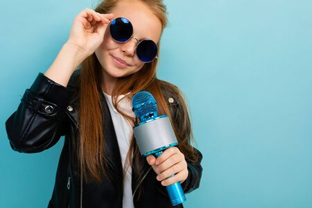 Young female with brown hair in black jacket, blue sunglasses with blue microphone isolated on blue background