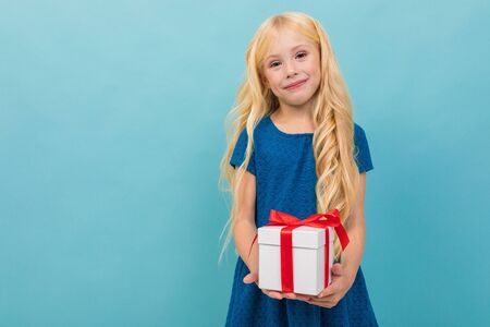 cute blond child in a dress with a gift in his hands on a light blue background with copy space.