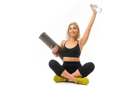 Caucasian sport woman with blonde hair sits with sports mat and smiles isolated on white background
