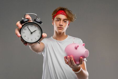 Portrait of young caucasian man in red sunglasses, white t-shirt posing on camera with pink pig money box isolated on grey background