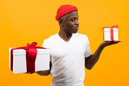 cute surprised black african man with a smile in a white t-shirt holds two boxes a gift with a red ribbon for a birthday on a yellow studio background. Stock Photo