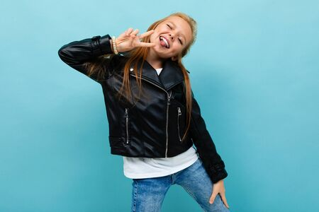 Cool teenager girl in black jacket and jeans smiles isolatedd on blue background. Stock Photo