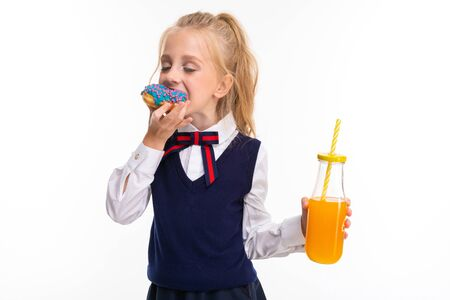 Pretty schoolgirl eats a donut and drinks juice isolated on white background. Imagens