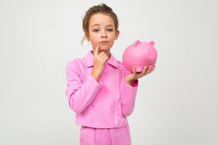 finance. portrait of a girl in a pink suit holding a piggy bank on a white background with copy space. Zdjęcie Seryjne