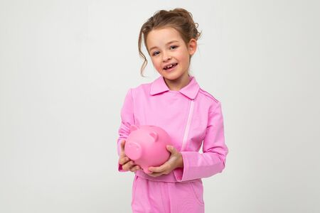 finance. young cute girl in a pink suit holds a piggy bank on a white background with copy space.