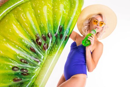 Handsome blonde caucasian female stands in swimsuit with rubber beach kiwi mattress and drinks juice isolated on white background