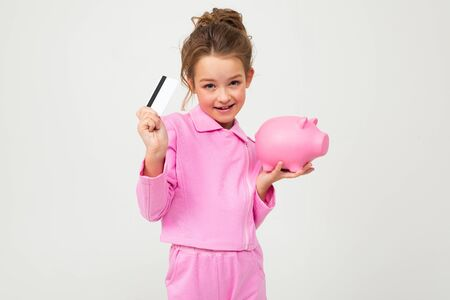 portrait of a bright girl in a pink suit holding a piggy bank and a credit card with a mockup on a white background. Zdjęcie Seryjne