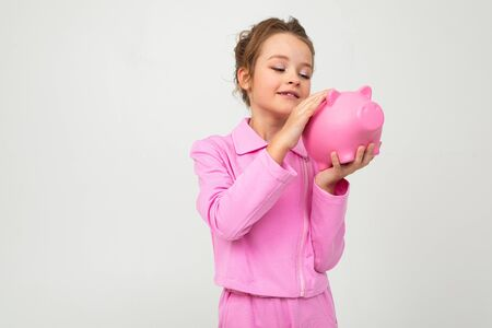 girl in a pink suit holds a piggy bank on a white background with copy space.