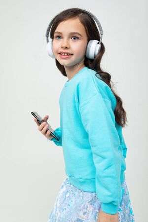 European cute young girl in a blue blouse enjoys music in large stylish headphones with a phone in her hands in a studio of light tones.