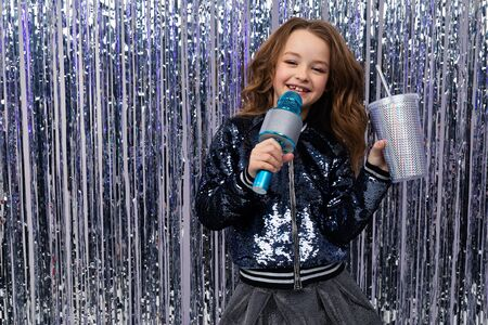 beautiful attractive girl in a talent contest with a microphone and a glass of drink on a shiny background.