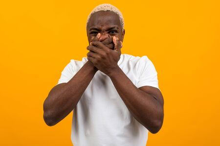 handsome american guy in a white t-shirt covers his mouth with his hands on a yellow isolated background.