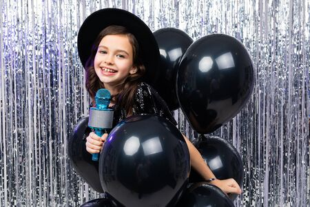 young fashionista in a black hat with brim with a microphone in her hands at a party.