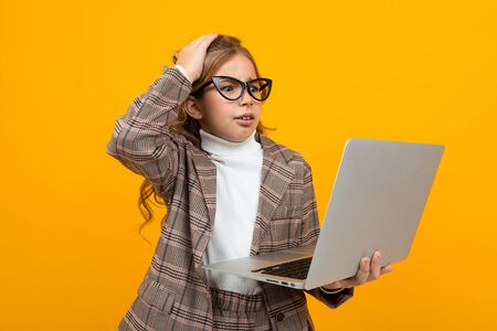 smart caucasian girl with glasses in a business suit and a jacket with a laptop in hand on a yellow background.