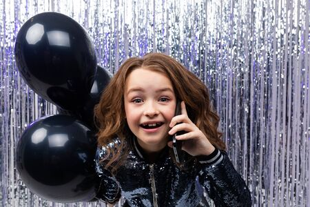 black Friday. young funny caucasian girl with helium black balloons in hand communicates on the phone on a shiny tinsel background.