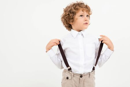 Caucasian pretty boy with curly hair in white shirt with black suspenders stands isolated on white background