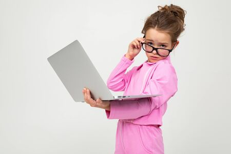 serious attractive girl with glasses in a pink suit with a laptop on a white studio background.