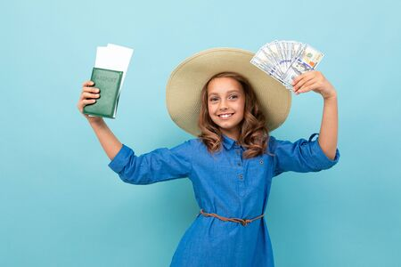Caucasian girl with wavy brown hair in blue dress, big hat shows a passport with tickets, money and rejoices isolated on blue background