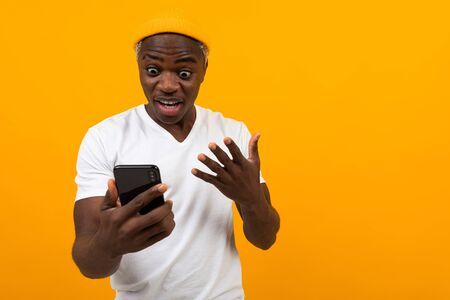 black american man looks in surprise on the phone on an orange background. Reklamní fotografie