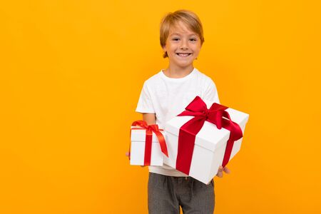 Caucasian boy holds many white boxes with gifts and rejoices, portrait isolated on yellow background. Reklamní fotografie
