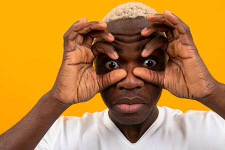 surprised black african young man covers his face with his hands and bulges his eyes on a yellow background.