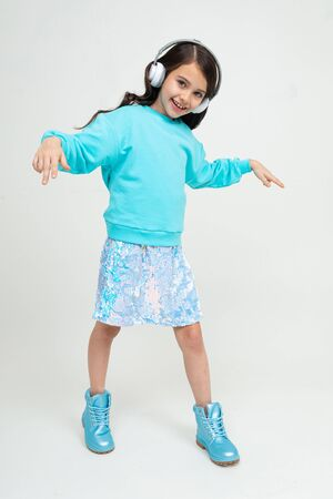 funny stylish young girl dancing to the music on headphones in an isolated studio.