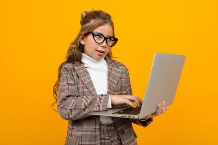 smart caucasian schoolgirl with glasses in a business suit and a jacket with a laptop in hand on a yellow background. Zdjęcie Seryjne