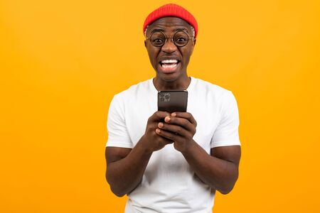 American man very surprised holding a smartphone in his hands on a yellow background with copy space. Zdjęcie Seryjne