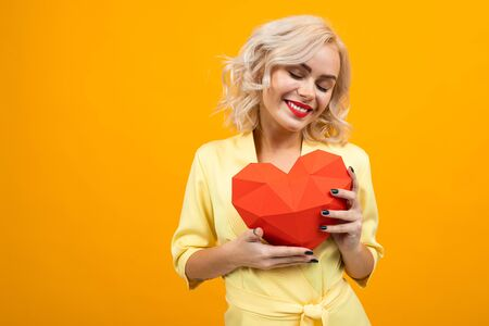 Cheerful young woman with short blonde hair smiles and holds a big red heart isolated on orange background. Zdjęcie Seryjne - 139903023