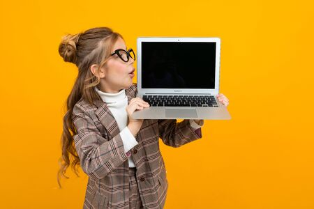 surprised beautiful girl in a classic jacket holds a laptop with a mock-up display forward on a yellow background with copy space.