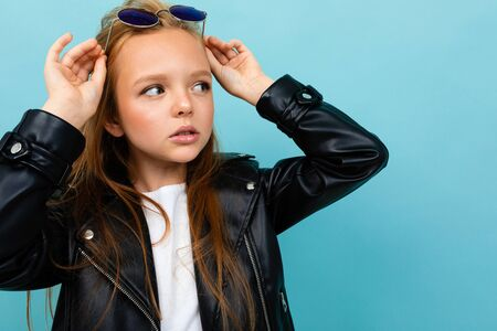 Pretty caucasian teenager girl with long brown hair in black jacket and denim jeans holds black sunglasses isolated on blue background.
